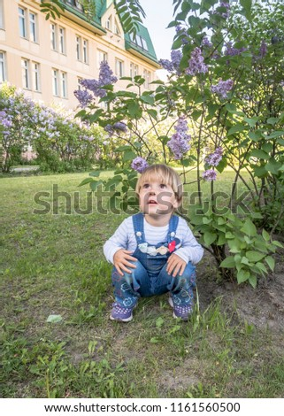 The child crouched under a flowering bush looks up in surprise