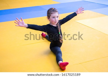 The child does gymnastics in a black leotard. A schoolgirl takes part in dance competitions. Little girl is sitting on the splits in the gym.