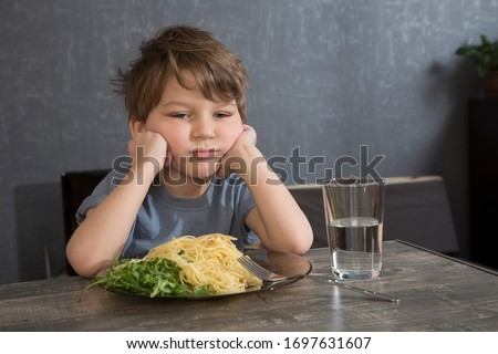 The child doesn't want to eat. The boy eats spaghetti. Poor appetite. Healthy diet. Refuses to eat. A disgruntled child at lunch.