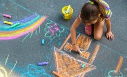 The child draws a house and a rainbow on the asphalt with chalk. Selective focus. Kids.