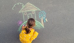 The child draws a house on the asphalt. Selective focus. kid.