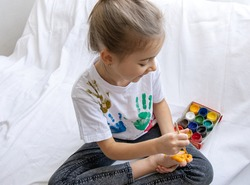 The child draws a pattern on his foot with a brush. A funny drawing with bright colors on the body.