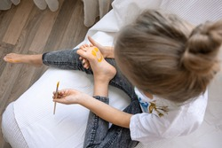 The child draws a pattern on his foot with a brush. Funny drawing with paints on the body.