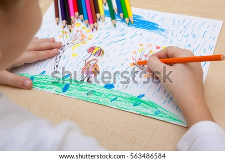 The child draws a pencil drawing of the peace. #563486584
