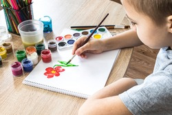 The child draws gouache on a white sheet and jars of paint are on the table. Hobbies and entertainment for children. Close-up.