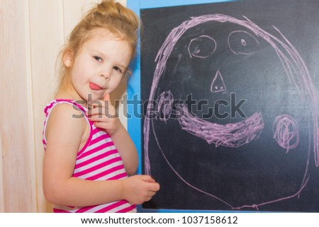 The child draws his mother on the slate. A little girl is drawing on the blackboard. #1037158612