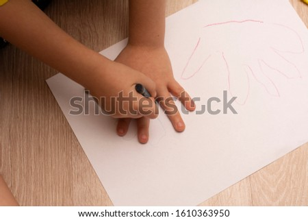 The child draws on the floor. A piece of white paper with a hand drawing on it.