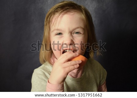 The child eats an orange. Girl with an orange. Portrait of a girl with fruit. Appetizing eating citrus. #1317951662
