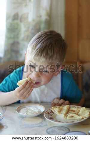 The child eats pancakes for Breakfast