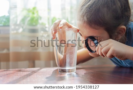 The child examines the water with a magnifying glass in a glass. Selective focus. Kid.