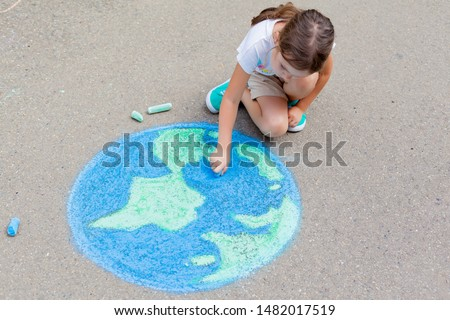 the  child girl draws a planet, globe with a map of the world with  chalk on the asphalt. Children's drawings, paintings and concepts. art, be creative when you return to school. earth, Peace day #1482017519
