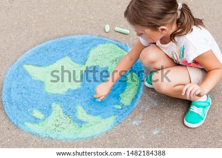 the  child girl draws a planet, globe with a map of the world with  chalk on the asphalt. Children's drawings, paintings and concepts. art, be creative when you return to school. earth, Peace day #1482184388