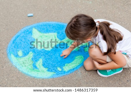 the child girl draws a planet, globe with a map of the world with chalk on the asphalt. Children's drawings, paintings and concepts. art, be creative when you return to school. earth, Peace day  #1486317359