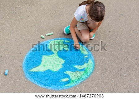 the child girl draws a planet, globe with a map of the world with chalk on the asphalt. Children's drawings, paintings and concepts. art, be creative when you return to school. earth, Peace day #1487270903