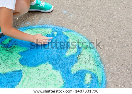 the child girl draws a planet, globe with a map of the world with chalk on the asphalt. Children's drawings, paintings and concepts. art, be creative when you return to school. earth, Peace day  #1487331998