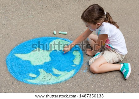 the child girl draws a planet, globe with a map of the world with chalk on the asphalt. Children's drawings, paintings and concepts. art, be creative when you return to school. earth, Peace day  #1487350133