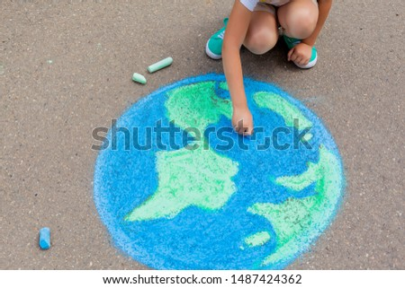 the child girl draws a planet, globe with a map of the world with chalk on the asphalt. Children's drawings, paintings and concepts. art, be creative . earth, Peace day concept