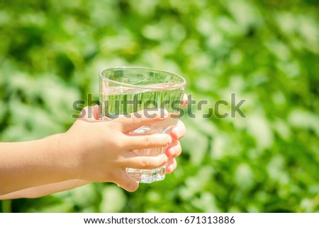 The child gives a glass of water. - Shutterstock ID 671313886