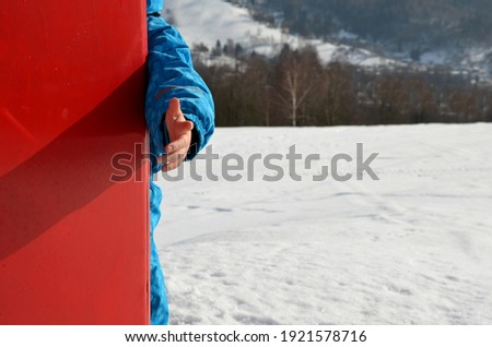 the child hits the foam barrier at high speed on a pole near the ski slope. Safety protection of an obstacle when a child on a ski course, school gym, survives a hard impact, blue winter jacket, hand Stock fotó ©