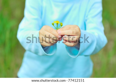 The child holds a flower