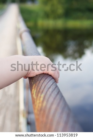 The child holds a hand an iron rope