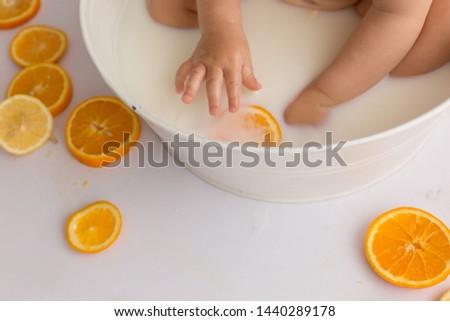 the child holds an orange. orange. child's hand #1440289178