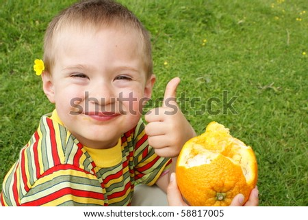 The child holds orange ,background grass - stock photo