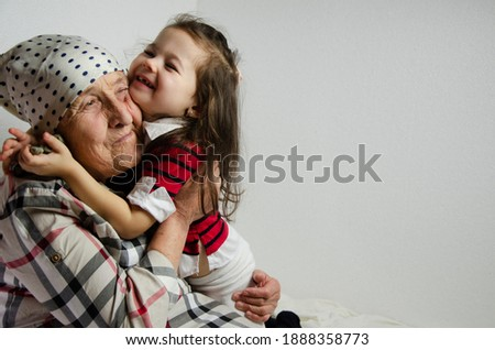 The child hugs the grandmother. Hugs of a child with a grandmother. Happy grandmother hugs the kid close-up. Happy family. Children's laughter. Trust in the family. Granddaughter hugs grandmother