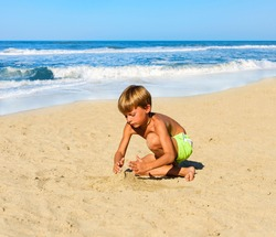 The child in a bathing suit plays on the sand at the beach on a sunny day. In the background the beach and the ocean waves.