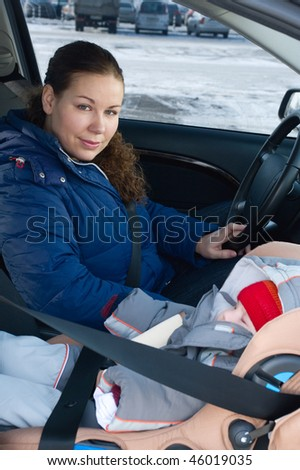 The child in a safety seat near to mother who sits on forward sitting of the car. Child not in focus