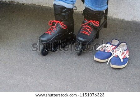 the child in shod black rollers with red laces and blue moccasins for dressing up shoes on a skating rink where people go for a drive, a theme of sports and recreation  #1151076323