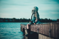 The child in the gas mask is sitting on the platform at the lake. Environment pollution. Coronovirus epidemic.
