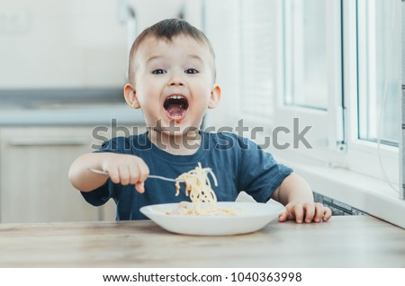 The child in the kitchen at the table eating macaroni and interesting view from the top #1040363998