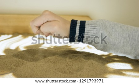 the child is engaged with sand