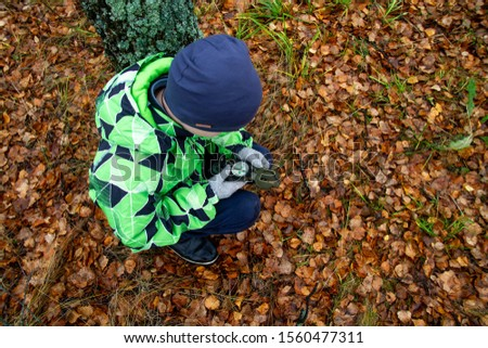 The child is guided by a compass in the woods. Autumn. A teenage boy got lost. Look for a way out of the woods.
