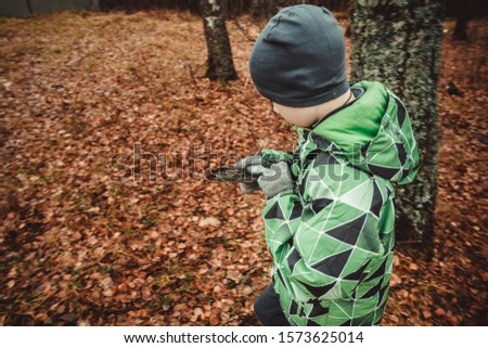 The child is guided by a compass in the woods. Autumn. A teenage boy got lost. Look for a way out of the woods. Lost alone in a strange place.