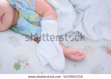 The child is ill with a fever, lying in a hospital bed and giving the saline solution by hand and then wrapping it with a cloth.