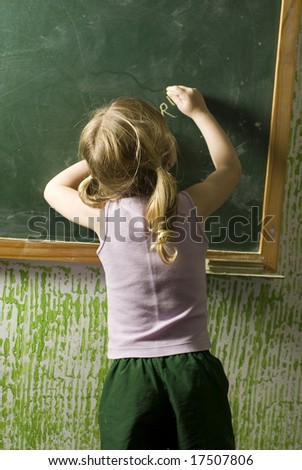 The child is in a school room.  She is doing something on the chalkboard.  Vertically framed shot.