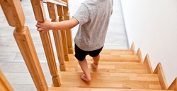 The child is moving down through the wooden stairs in home