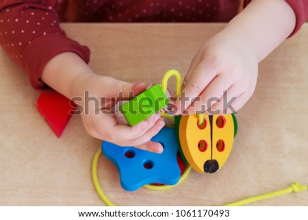 The child is playing with a wooden developing toy. Hands of the  #1061170493