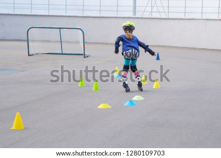 the child is roller skating on the sports field, the theme of sport and recreation  #1280109703