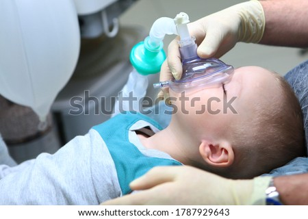 The child is under General anesthesia. Treatment of baby teeth.The device of artificial ventilation of lungs.Copy space. Stock foto ©