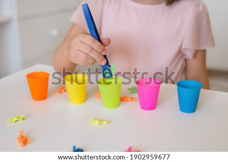 The child learns colors. A little girl sorts animal figures by color. Preschool education and development of children. The girl holds the tongs in her hands. Learn colors. Stockfoto ©