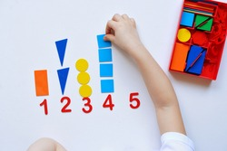 The child learns Number line and geometric shapes. The preschooler works with Montessori material. Educational logic toys for kid's. Children's hands close-up. Montessori Games for Child Development