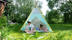 The child learns to read. The boy reads the first children's book on syllables. Children spend summer holidays in the countryside in the garden. Ideas of children's activities without parents.