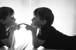 the child looks at himself in the mirror on a dark night