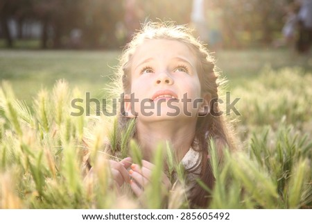 The child looks up. Beautiful girl with long hair raised her eyes to the sky. Dreaming child.