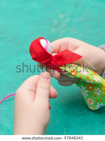 The child makes a traditional toy from different rags