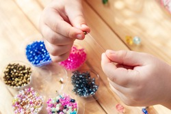 The child makes jewelry with his own hands, stringing colorful beads on a thread.