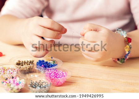 The child makes jewelry with his own hands, stringing colorful beads on a thread. Foto d'archivio ©